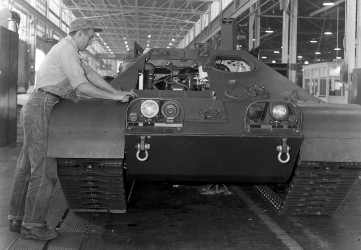 An assembly line worker tightens the bolts securing the transmission cover. On the re-powered M50A1 this cover was replaced with a louver.