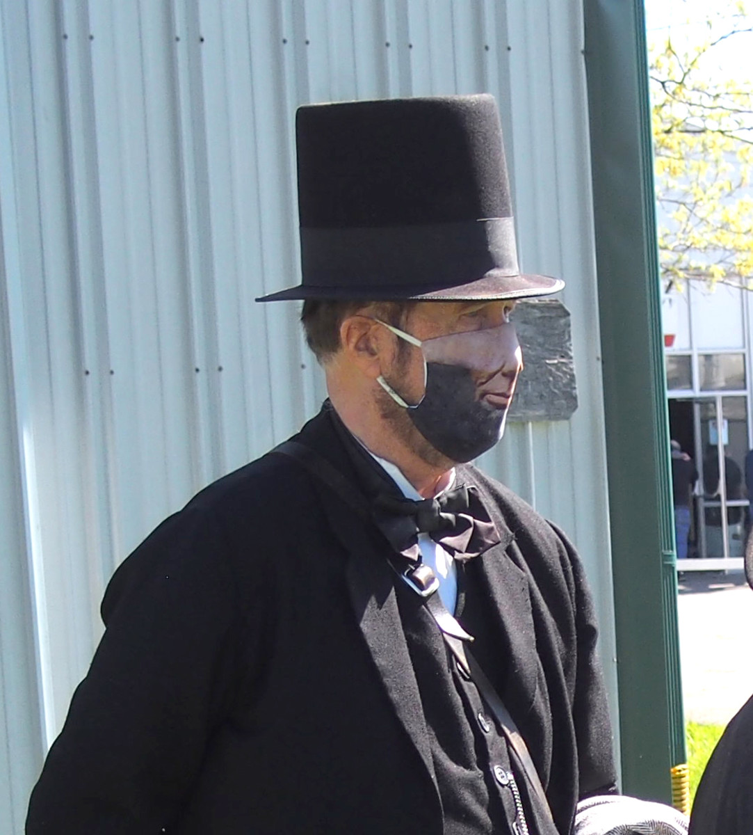 Lincoln impersonator wearing a mask depicting a nose, mouth, and beard.