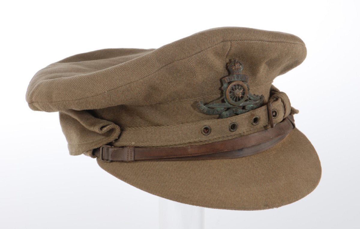 This khaki wool twill cap with cloth-covered visor has a folding neck cape with cloth chinstrap adjustable by a buckle and metal eyelets in addition to the traditional brown leather chin strap.