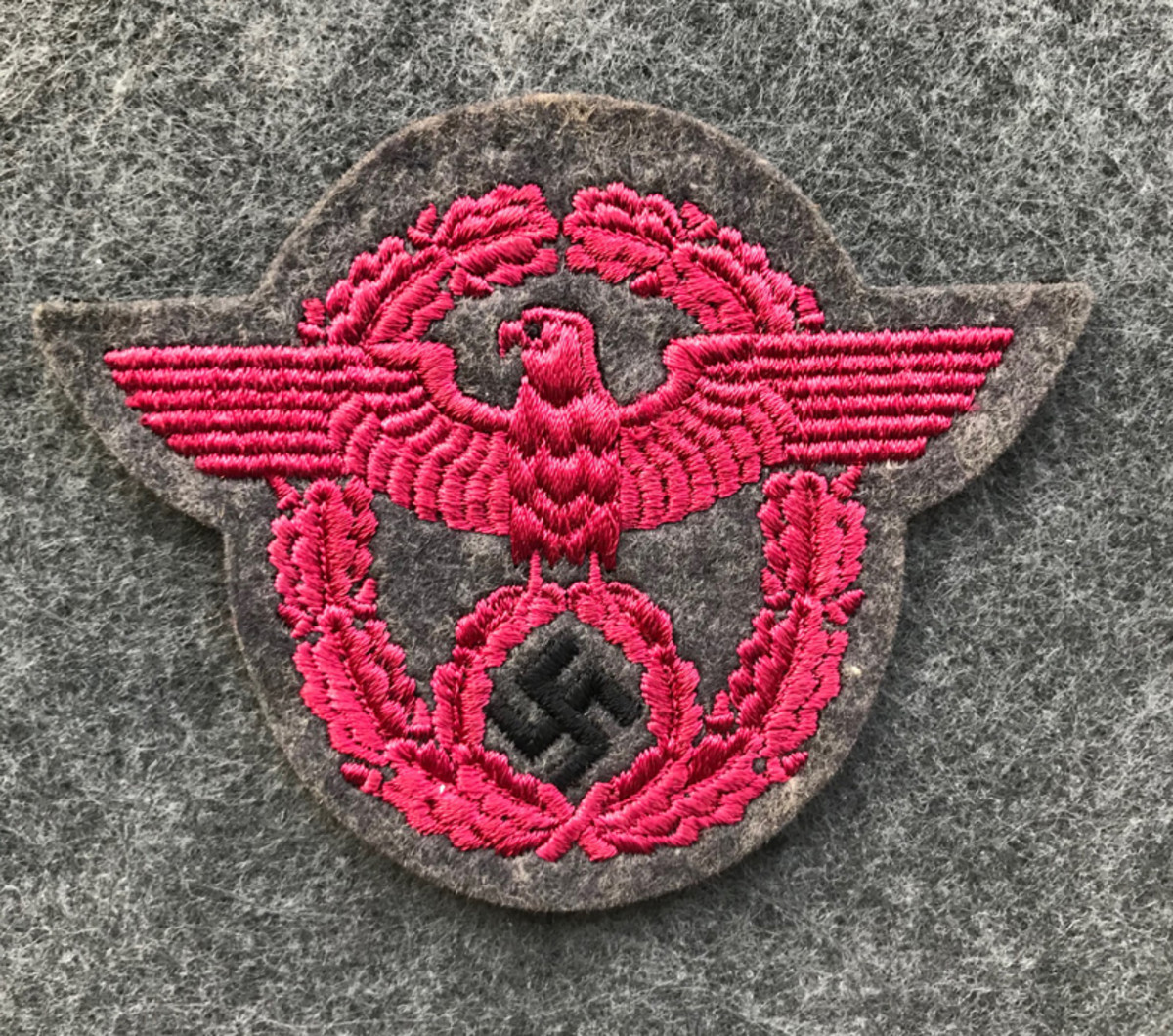A German Enlisted Feuerschutzpolizei/Fire Protection Police sleeve eagle. This type of police patch is constructed with a machine embroidered pink eagle with a black swastika on grey wool cloth.