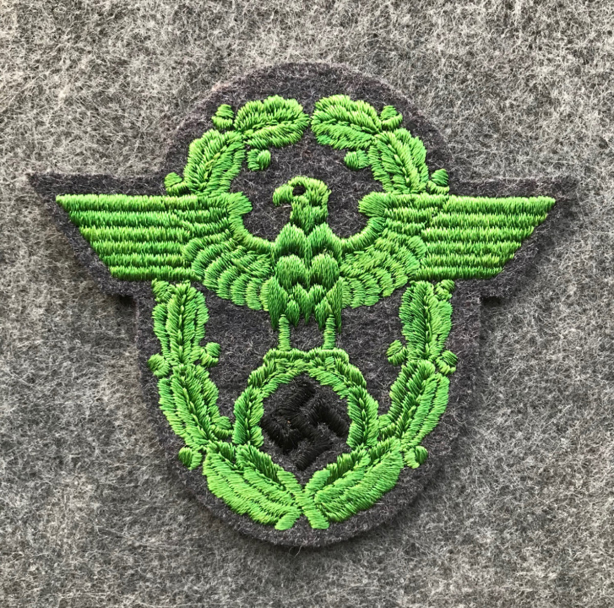 A German Enlisted Schutzpolizei Municipal police sleeve eagle. This type of police patch is constructed with a machine embroidered bright green national eagle with a black swastika on bluish-green wool cloth. This type of German WWII police patch retails for around $55-$70.
