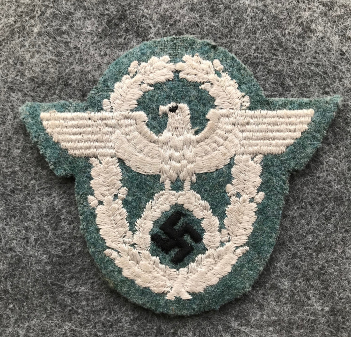 A German Enlisted Ordnungspolizei/Police Administration sleeve eagle. This type of police patch is constructed with a machine embroidered silver/grey eagle with a black swastika sewn on green wool cloth. This type of police patch retails for around $50-$70.