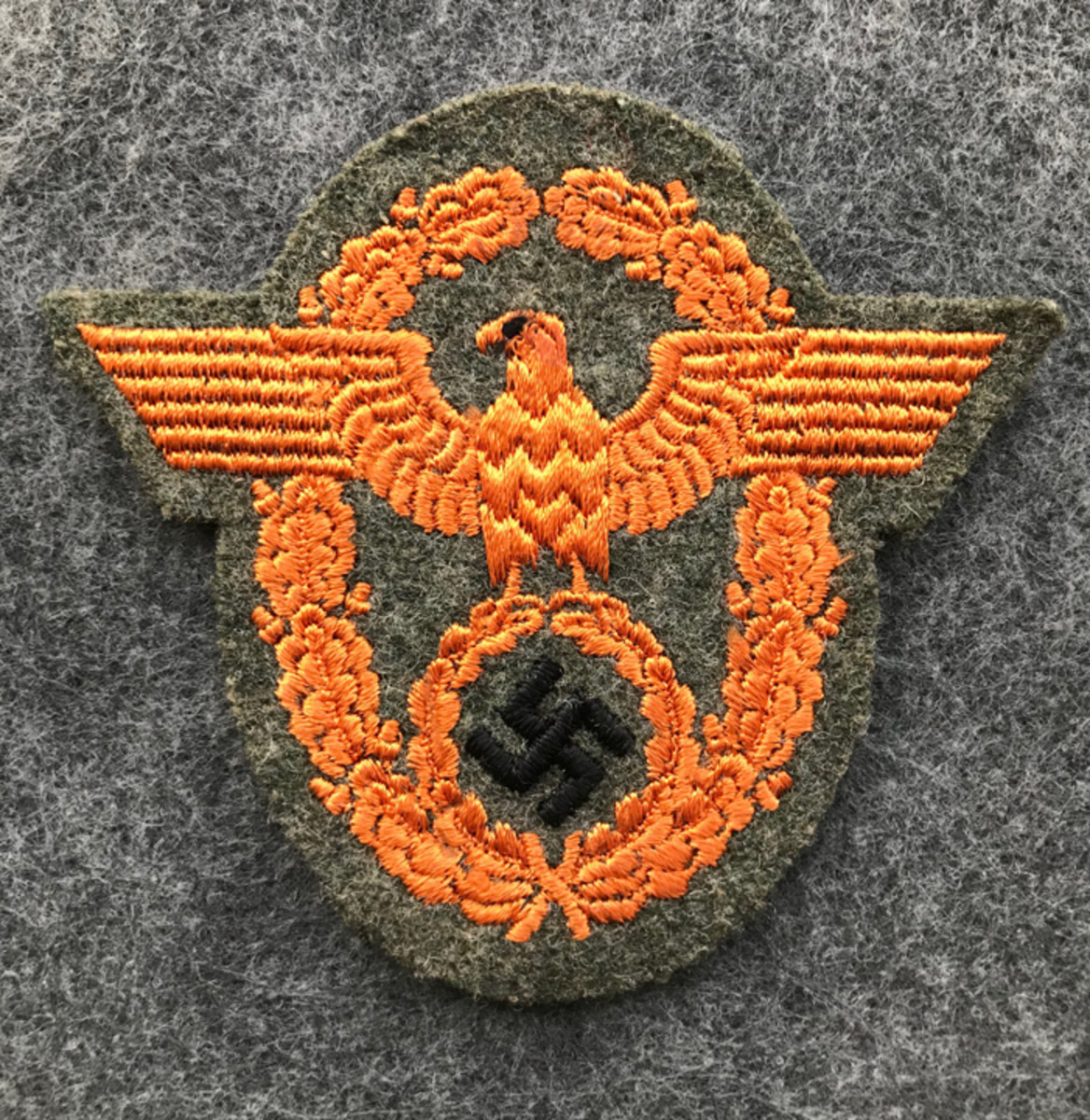 A German Enlisted Gendarmerie sleeve eagle. This type of police patch is constructed with a machine embroidered orange eagle with black swastika on grey wool cloth. This type of German WWII police patch retails for around $50-$70.