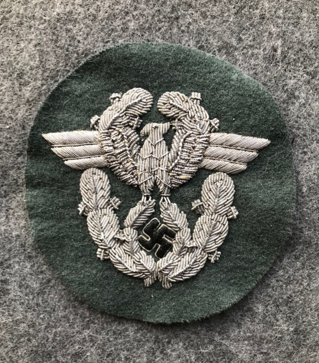 A German Officer Police sleeve eagle. This type of police patch is constructed with the national eagle hand embroidered with twisted and flat silver bullion wires and black swastika on police green wool cloth. This type of German WWII police patch retails for around $160-$200.