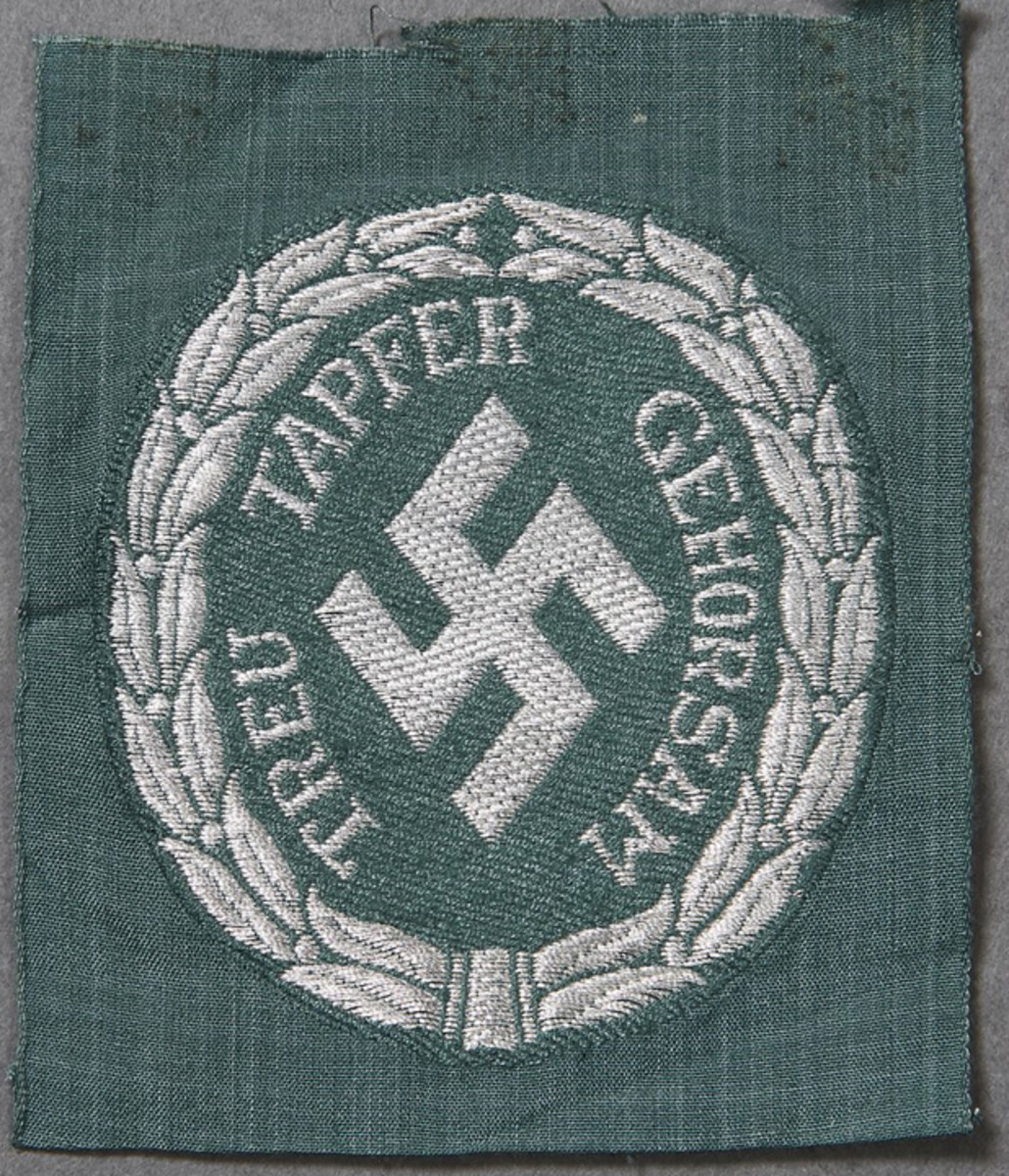 A German Schutzmannschaft (Schuma) Auxiliary Police sleeve shield. This type of police patch is BeVo machine woven in silver flat wire on blue green cloth. The design is of a wreath and diamond shaped swastika with the words Treu/Loyal, Tapfer/Brave and Gehorsam/Obedience. This type of German WWII police patch retails for around $150-$200.