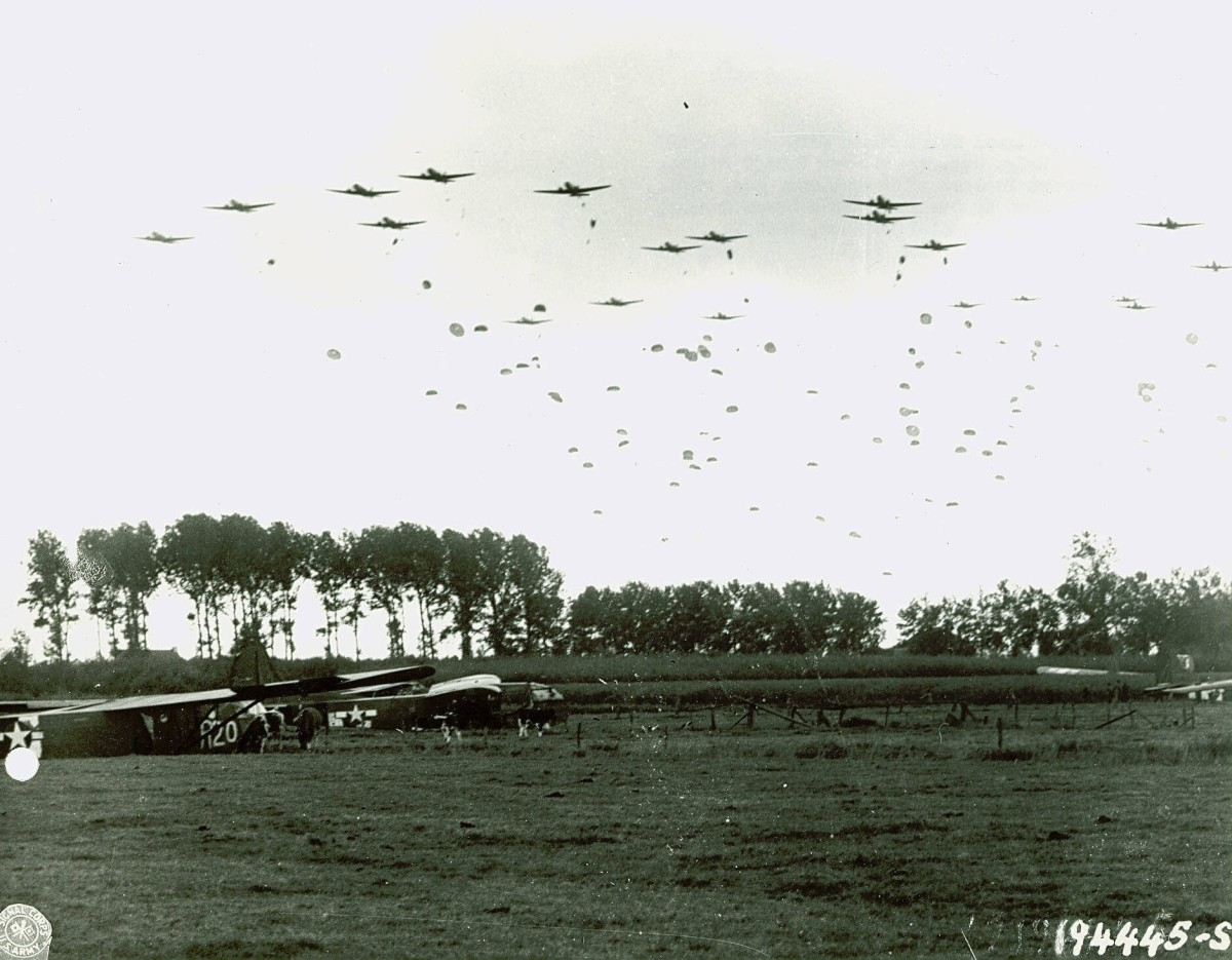 Photo of C-47s dropping paratroopers over a field strewn with gliders.