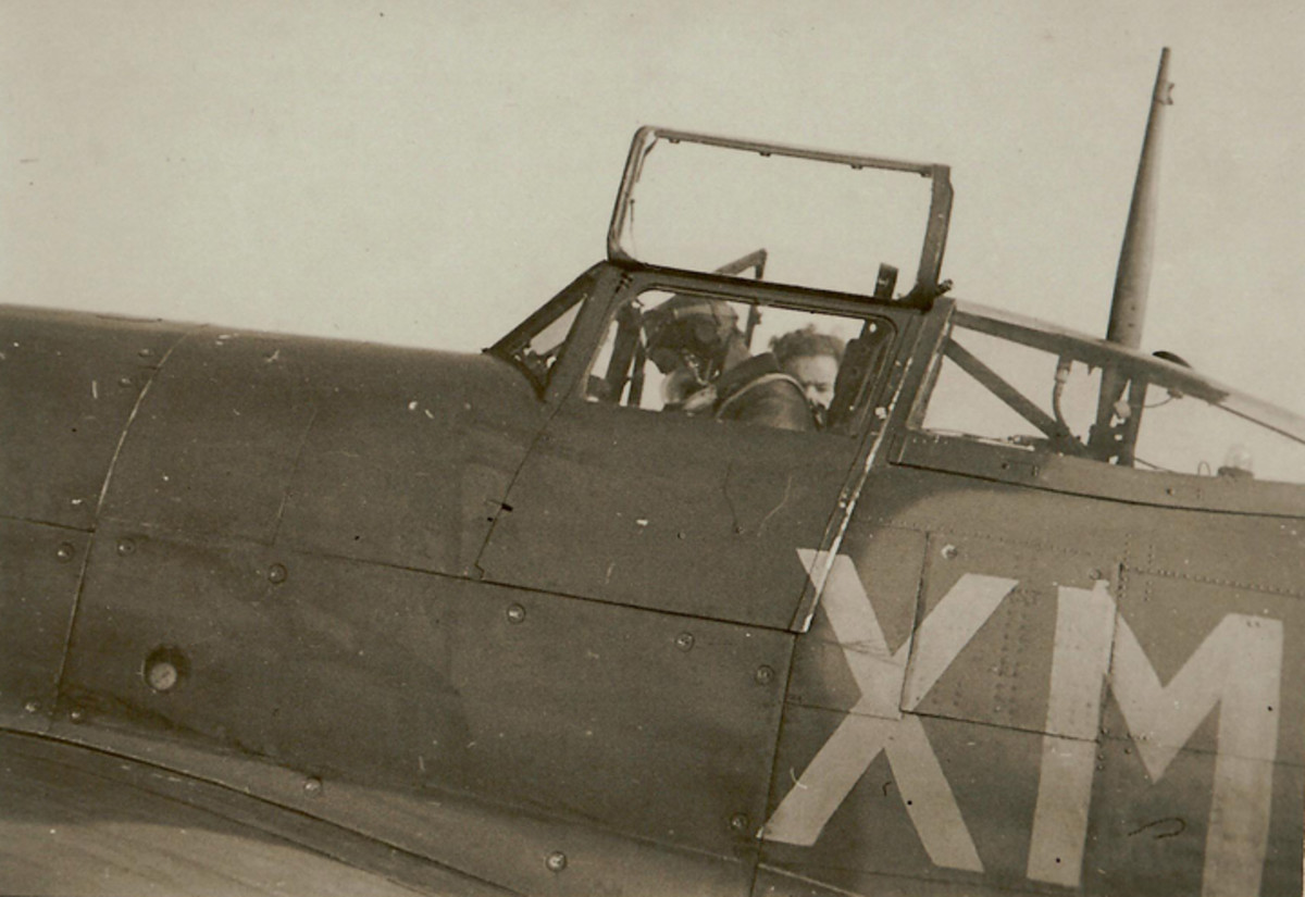 """Terry O'Connor, a wartime buddy of McBean, is seen here in the cockpit of his Typhoon fighter bomber. Terry and Mac flew many sorties together. The Squadron code for 182 Sqn (i.e., """"XM"""") is clearly seen."""