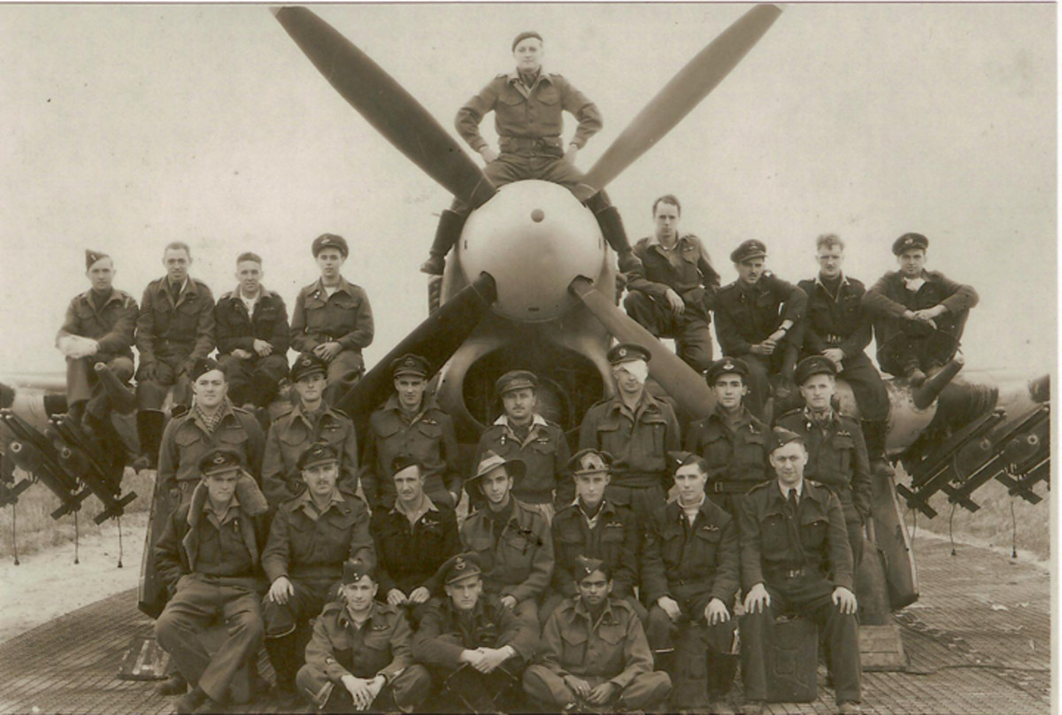"""This picture of the """"boys from our squadron"""" (182 RAF) is dated 1944. Walter McBean sent this photo to his mother back in Australia. Judging by the background buildings and where the squadron was stationed, this photo was most likely taken at the squadron's base of Hurn, near Bournemouth, England, around the time of D-Day. Walter is sitting on the port wing, second from the right with his hands on his knees."""