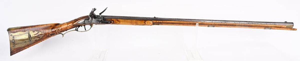 1999 Judson Brennan (Delta Junction, Alaska) full-stock 37-inch .50-caliber flintlock rifle with masterfully carved fiddleback maple stock, handcrafted brass furniture and swamped barrel engraved 'Judson Brennan #93'