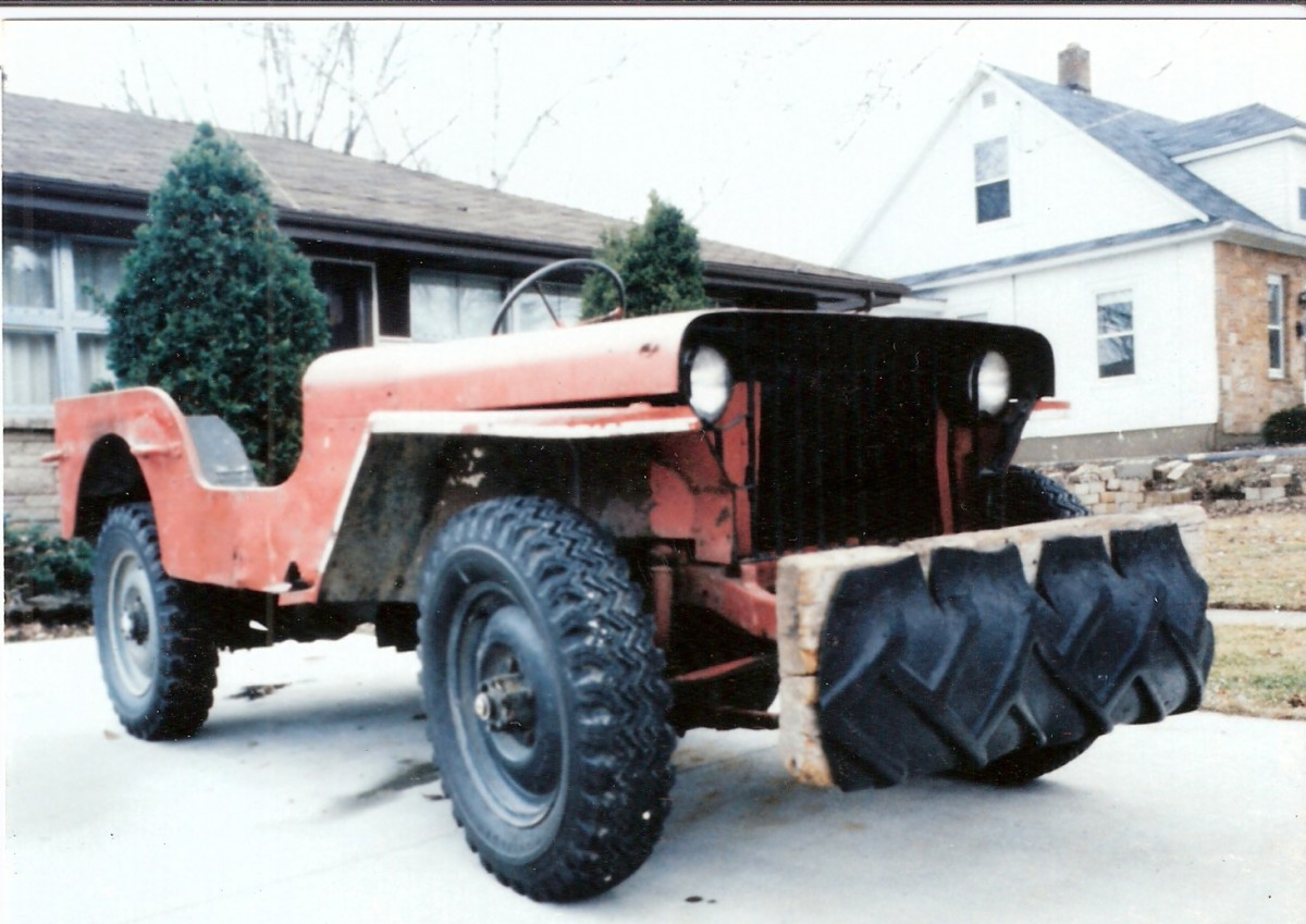 No. 103677 prior to restoration. Red jeep with wooden front bumper and no grille or windshield--pretty rough.