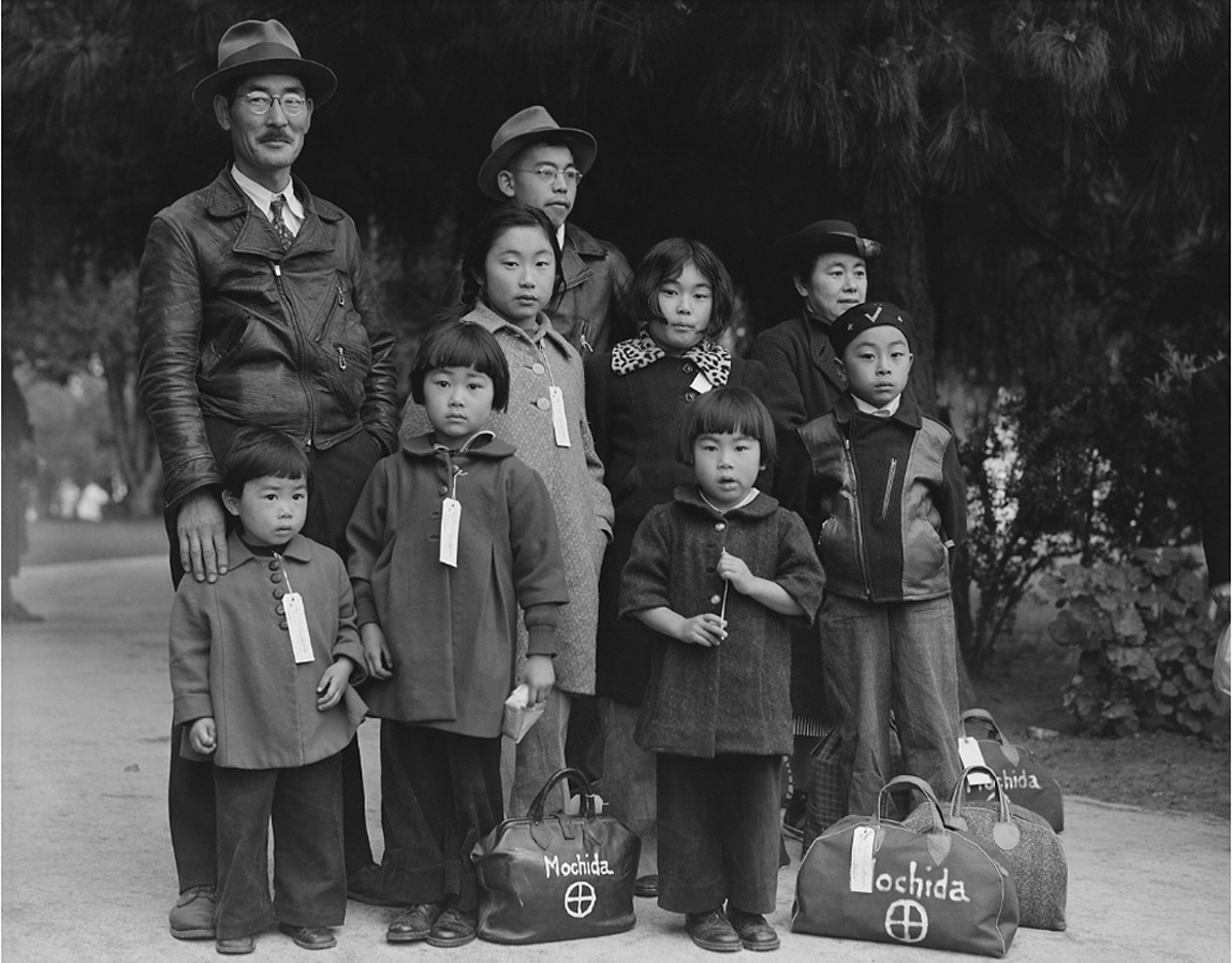 The Mochida family, wearing identification tags awaits a bus. They were forced to leave their two-acre nursery and greenhouse in Eden, California, May 1942.