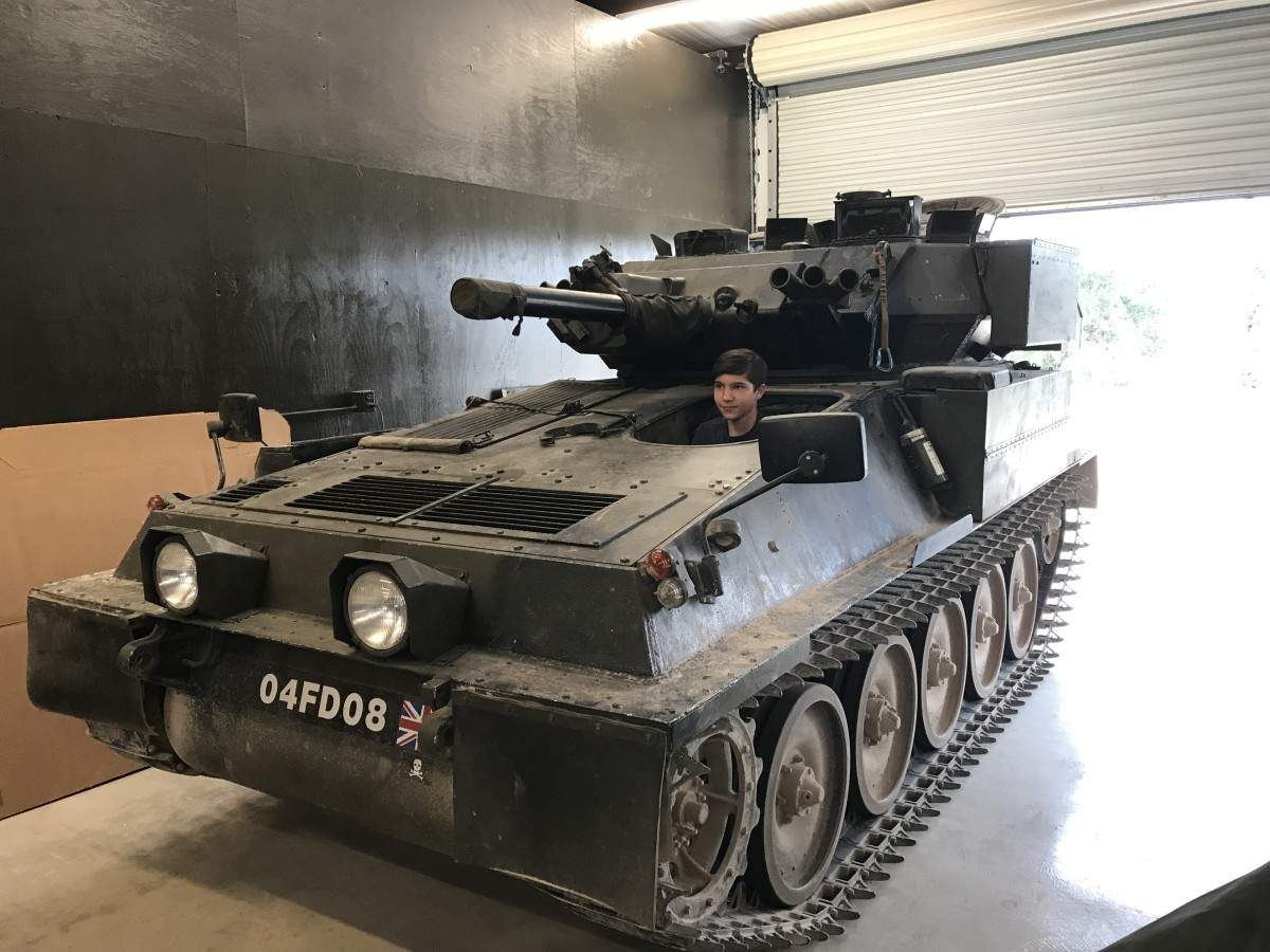 """The DriveTanks crew encourages """"hands-on"""" learning. Here, Jesse got the feel of the driver's seat of a British Scorpion FV101 armored reconnaissance vehicle that saw service in the Falklands and Gulf War."""